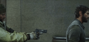 In The Last of Us, a firefly pointing his gun at Joel actually has good trigger discipline, keeping his finger next to but not on the trigger.: In The Last of Us, a firefly pointing his gun at Joel actually has good trigger discipline, keeping his finger next to but not on the trigger.