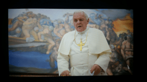 """In """"The Two Popes"""" (2019), during his conversation with Bergoglio about divine judgement and his resignation from the papacy, Pope Benedict is seen in multiple shots with Michaelangelo's """"Last Judgement"""" in the background. The portion of the fresco shown depicts the souls of the Damned.: In """"The Two Popes"""" (2019), during his conversation with Bergoglio about divine judgement and his resignation from the papacy, Pope Benedict is seen in multiple shots with Michaelangelo's """"Last Judgement"""" in the background. The portion of the fresco shown depicts the souls of the Damned."""