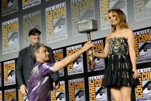 "feministscoundrel: This photo means a lot to me. And I'll tell you why.  Natalie Portman, as we know, was shut out of Marvel. She chose not to sign any new contract not just because of the way her character was treated (though there is that) but because Thor: The Dark World was slated to be the first Marvel movie directed by a woman, her friend (and eventual Wonder Woman director) Patty Jenkins. Portman hadn't planned on being in The Dark World, but lept at the chance to be a part of feminist history and to be directed in what would have beenJenkin's first film since her 2003 Oscar-winning Monster. Portman signed a new contract with Marvel. They fired Jenkins soon after. Portman was crushed because she essentially had been duped into a contract for a film that would keep her away from her young son and force her back into a one-dimensional role under yet another male director. And we all remember how awful that movie was.  When it came time for the third Thor movie, they tried to get Portman under contract again. And she said no. Marvel decided to spin the story to make it seem like it was all their idea. At first, they went for the lame and nonsensical:  When Marvel Studios President Kevin Feige was asked about why she wouldn't be in the third film, and said there were ""many reasons, many of which are in the film, so you will see that"" continuing with ""There are only a couple of scenes on Earth in this movie. The majority, 95 percent of the movie, takes place in the cosmos."" (x) Seeing as The Dark World also took place in space, this answer didn't have a lot of credibility. When Portman said she was ""done"" with the Marvel Universe, Feige got vicious in interviews, telling reporters that Valkyrie was in Ragnorak to be better than Jane Foster and a better match for Thor.  ""We wanted Thor to encounter somebody that was near his equal and that his relationship with Jane may have evolved in unexpected ways in between The Dark World and Ragnarok, and we wanted to pit him against a character who was much more his equal and in many ways his superior."" (x) Feige implies that A) Valkyrie was in Ragnorak to be a romantic interest for Thor, B) Valkyrie is better and more powerful than Jane Foster, and C) Jane Foster was always Thor's inferior.  What's ridiculous is that Ragnorak had a ""sorry Jane dumped you"" throwaway line to explain Portman's absence. And instead of saying that Jane and Thor broke up in interviews, a line that does not spoil literally anything about the film, Feige chose to attack Jane's strength and capability, which would have been a very special dig at Portman.  Do you want to know what none of this sounds like? Taika Waititi's opinion. Waititi is a master storyteller who does not sacrifice his feminist views for laughs. You can bet that Feige's ridiculous slams on Portman and her character Jane– disguised as ""promotion"" for WAITITI'S FILM– would have troubled him immensely. This is a man with a Māori father, who had to use his mother's maiden name– Cohen– for earlier work because an indigenous last name kept him away from opportunity. This man does NOT fuck around with entertainment that gets its power off of sexism and inequality. He knows from experience just how infuriating it is when it comes to directors missing out on opportunities because they aren't a white man.  So how does he fix this? How does he fix the idea that Jane Foster can't go to space, or that she's not powerful enough for Thor, the god of thunder?  He makes her Thor.  Waititi saw Portman / Jane Foster's name dragged through the mud by Kevin Feige in order to promote his movie, and when he got hired to direct again, he decided to right those wrongs. This picture means everything. He is on his knee, handing her Thor's hammer, essentially saying, you will never have to go through that shit with me. With me, you're a god. And the expression on her face, after Marvel attempted to break her, doesn't need words.  What a photo. What a film. What a man.  : INTERNATIONAL  INTERNATIONAL  SAN DIEGO  AN DIE  ECON CONCON CON  INTERNA  INTER  INTERNATIONAL  1N DIEG0  OIEGO  SAN DIEGO  CON  OUG NO  CON  DIEGO  CON  INTERNATIONAL  ONAL  INTERNATIONAL  IN E WATIONAL  TERNATIONA  SAN DIEGO  CON  SAN OIEG0  0 93  eONCON CO  SAN OIEG  N OIEG  CO  INTERNATIO  COMICE  CO  OM feministscoundrel: This photo means a lot to me. And I'll tell you why.  Natalie Portman, as we know, was shut out of Marvel. She chose not to sign any new contract not just because of the way her character was treated (though there is that) but because Thor: The Dark World was slated to be the first Marvel movie directed by a woman, her friend (and eventual Wonder Woman director) Patty Jenkins. Portman hadn't planned on being in The Dark World, but lept at the chance to be a part of feminist history and to be directed in what would have beenJenkin's first film since her 2003 Oscar-winning Monster. Portman signed a new contract with Marvel. They fired Jenkins soon after. Portman was crushed because she essentially had been duped into a contract for a film that would keep her away from her young son and force her back into a one-dimensional role under yet another male director. And we all remember how awful that movie was.  When it came time for the third Thor movie, they tried to get Portman under contract again. And she said no. Marvel decided to spin the story to make it seem like it was all their idea. At first, they went for the lame and nonsensical:  When Marvel Studios President Kevin Feige was asked about why she wouldn't be in the third film, and said there were ""many reasons, many of which are in the film, so you will see that"" continuing with ""There are only a couple of scenes on Earth in this movie. The majority, 95 percent of the movie, takes place in the cosmos."" (x) Seeing as The Dark World also took place in space, this answer didn't have a lot of credibility. When Portman said she was ""done"" with the Marvel Universe, Feige got vicious in interviews, telling reporters that Valkyrie was in Ragnorak to be better than Jane Foster and a better match for Thor.  ""We wanted Thor to encounter somebody that was near his equal and that his relationship with Jane may have evolved in unexpected ways in between The Dark World and Ragnarok, and we wanted to pit him against a character who was much more his equal and in many ways his superior."" (x) Feige implies that A) Valkyrie was in Ragnorak to be a romantic interest for Thor, B) Valkyrie is better and more powerful than Jane Foster, and C) Jane Foster was always Thor's inferior.  What's ridiculous is that Ragnorak had a ""sorry Jane dumped you"" throwaway line to explain Portman's absence. And instead of saying that Jane and Thor broke up in interviews, a line that does not spoil literally anything about the film, Feige chose to attack Jane's strength and capability, which would have been a very special dig at Portman.  Do you want to know what none of this sounds like? Taika Waititi's opinion. Waititi is a master storyteller who does not sacrifice his feminist views for laughs. You can bet that Feige's ridiculous slams on Portman and her character Jane– disguised as ""promotion"" for WAITITI'S FILM– would have troubled him immensely. This is a man with a Māori father, who had to use his mother's maiden name– Cohen– for earlier work because an indigenous last name kept him away from opportunity. This man does NOT fuck around with entertainment that gets its power off of sexism and inequality. He knows from experience just how infuriating it is when it comes to directors missing out on opportunities because they aren't a white man.  So how does he fix this? How does he fix the idea that Jane Foster can't go to space, or that she's not powerful enough for Thor, the god of thunder?  He makes her Thor.  Waititi saw Portman / Jane Foster's name dragged through the mud by Kevin Feige in order to promote his movie, and when he got hired to direct again, he decided to right those wrongs. This picture means everything. He is on his knee, handing her Thor's hammer, essentially saying, you will never have to go through that shit with me. With me, you're a god. And the expression on her face, after Marvel attempted to break her, doesn't need words.  What a photo. What a film. What a man."