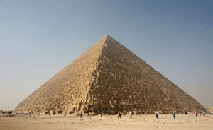 Apparently, Disappointed, and Fucking: ironychan:  This is the Great Pyramid of King Khufu. Everybody knows the Great Pyramid of King Khufu, but you probably don'tknow about the Shit Pyramids of his father, King Sneferu. This is a shame, because they are amazing. When King Sneferu came to the throne of Egypt, the cool thing that all the pharaohs had was a Step Pyramid, like the original one built by King Djoser and designed by Imhotep (not the mummy). King Sneferu could easily have had one one because his predecessor King Huni had died before hiscould be finished. All Sneferu had to do was step in and put the last few blocks on. But King Sneferu had a vision. He didn't want any old Step Pyramid. He was going to build Egypt's first smooth-sided pyramid, and make King Huni's pyramid way taller in the bargain. It didn't work. The core of Huni's pyramid couldn't handle the modifications and nowadays the Step Pyramid at Meidum looks like this: It's not on a hill - that's the outer layers of the pyramid that have fallen down all around it. The name of the structure in Arabic is Heram el-Kaddaab, which means something like The Sort-Of Pyramid. Anyway, King Sneferu was understandably disappointed and made his pyramid-builders start over from scratch at a different site. Apparently having learned nothingabout the Big Fat Nowhere that hubristic pyramid ambition was going to get him, thispyramid was designed to be even taller and pointier than the last effort! Tootall and pointy, in fact - the bedrock proved to be less stable than he might have hoped, and by the time the pyramid was half-finished stuff was already moving and cracking inside of it. There are ceilings in this pyramid that are to this daypartially held up by wooden beams. The builders seem to have panicked and decided that the only way to finish the pyramid without another disaster was to make the top half lighter than the bottom half. They did this by changing the angle of the slope, ending up with a pyramid tha