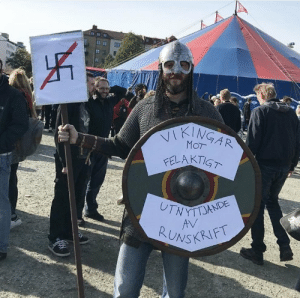 "rudolf-rokkr:  northern-seidmadr: petterwass: Best-dressed protestor att the anti-nazi/nazi rally in Gothenburg today.""Vikings against incorrect use of runic script""  THIS GIVES ME THE HAPPY  A bit of context for English-speaking heathens, reenactors, and other Viking enthusiasts, so that people don't make the mistake of believing the above protester is actually just complaining about runes. The Swedish neo-nazi movement Nordiska Motståndsrörelsen (NMR, 'Nordic Resistance Movement' (Wikipedia link)) uses the tīwaz/Týr rune as their logo, basically the way the American National Socialist Movement uses the ōþila rune. In Sweden (where in some places runes are even still taught in schools) people are particularly disturbed by the usurpation of their history and culture and fighting back to reclaim the Týr rune has been an effective rallying point for undermining the nazis' message by promoting knowledge about the things they lie about in order to stake a claim that they are representing their cultural heritage (link is in Swedish). The above protest was attended by members of Samfundet Forn Sed, Heathens United Against Racism (with some overlap between the two), and the guy pictured above was protesting with Vikingar Mot Rasism 'Vikings against racism.' The movement ""No Tiw for Nazis"" is on Facebook.: JE  INGAR  WYTTJANDE  ONSKRIFT rudolf-rokkr:  northern-seidmadr: petterwass: Best-dressed protestor att the anti-nazi/nazi rally in Gothenburg today.""Vikings against incorrect use of runic script""  THIS GIVES ME THE HAPPY  A bit of context for English-speaking heathens, reenactors, and other Viking enthusiasts, so that people don't make the mistake of believing the above protester is actually just complaining about runes. The Swedish neo-nazi movement Nordiska Motståndsrörelsen (NMR, 'Nordic Resistance Movement' (Wikipedia link)) uses the tīwaz/Týr rune as their logo, basically the way the American National Socialist Movement uses the ōþila rune. In Sweden (where in some places runes are even still taught in schools) people are particularly disturbed by the usurpation of their history and culture and fighting back to reclaim the Týr rune has been an effective rallying point for undermining the nazis' message by promoting knowledge about the things they lie about in order to stake a claim that they are representing their cultural heritage (link is in Swedish). The above protest was attended by members of Samfundet Forn Sed, Heathens United Against Racism (with some overlap between the two), and the guy pictured above was protesting with Vikingar Mot Rasism 'Vikings against racism.' The movement ""No Tiw for Nazis"" is on Facebook."