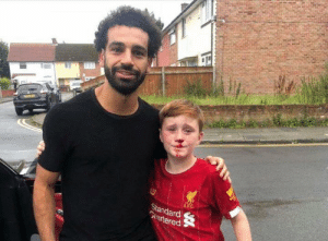 Liverpool fan Louis Fowler ran into a lamp post and fell to the ground breaking his nose as he and his brother ran to keep up with Mo Salah's car.‬  ‪Salah spotted that his young fan had got into difficulty, so turned back to check Louis was okay and then posed for photos. Louis' dad said Mo was very apologetic and so kind and compassionate towards the boys. ‬: LEC  Standard  Grartered Liverpool fan Louis Fowler ran into a lamp post and fell to the ground breaking his nose as he and his brother ran to keep up with Mo Salah's car.‬  ‪Salah spotted that his young fan had got into difficulty, so turned back to check Louis was okay and then posed for photos. Louis' dad said Mo was very apologetic and so kind and compassionate towards the boys. ‬