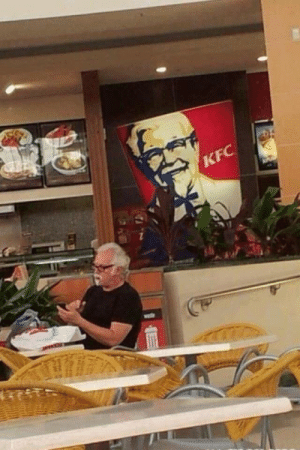 Leon Trotsky Proudly Lounging Near Propaganda Depicting His Contributions to Soviet Russia, Years Before His Fall From Power [1922, colorized]: Leon Trotsky Proudly Lounging Near Propaganda Depicting His Contributions to Soviet Russia, Years Before His Fall From Power [1922, colorized]