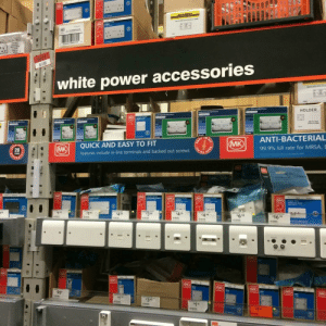 This sign at a certain depot of home improvement stores.: MK  MARBO  MOULDED BOOK DOURLE Sw  MK  KZERPALM  750  SOCKET  POUBLE  0os1702737>  0971  white power accessories  MOULDED BorDO  Double 2 ded P  HOLDER  Doble ded  OMKOLOGI PLUS  BANK PANE  FIT  ASY TO  ANTI-BACTERIAL  QUICK AND EASY TO FIT  MK  MK  20  YEARS  Features include in-line terminals and backed out screws  99.9% kill rate for MRSA,E  RAN  TO FIT  riabertng  MK  MK  MK LOGIK PLUS  (MK)|| LOCIC PLUS  seCET  MK)LOCIC PLUS  SOCRET  MK  Logie Pas  Mulioedia utet  98  198  498  39  426  498  TRIE  698  1698  566DABRPWHI  MK  WK  MK  MK  98  MK  MK  175  345  SAR  WRI  1 15  IGI  EASY This sign at a certain depot of home improvement stores.