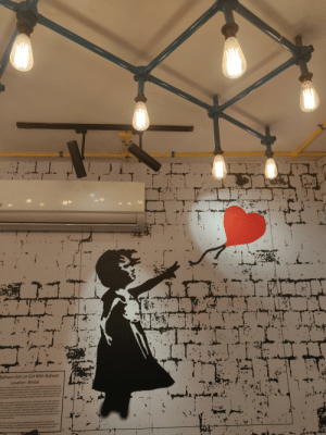 My favorite burger joint has used Banksy's art as wallpaper, there's his art all over with a small box in the corner crediting him & explaining the piece.: MM  Balloon Girl, or Girl With Balloon  Location : Bristol  or Girl With Balloon, is one of Banksy's most notable works, demonstrating  U stencil technique Banksy has become renowned for the world over. The work  sed as an unsigned and signed print in 2004/2005; its relatively low edition size  es to its desirabdity, there are just 150 Girl With Balloon signed prints, and 600  t is perhaps the most sought-after image for Banksy collectors, old and new.  epicts a young girl, whose hair and dress are blowing in the wind, reaching  sing a red, heart-shaped balloon that has slipped from her grasp, fying out  ered balloon is an archetypal smbol many of us connect with, as the only  in the work, mare than a child's toy, the red balloon evokes fragility of  for innocence dreams, hope and love. Whether you see the girl as losing  rabout to catchit, the meaning can be Interpreted as a loss of innocence,  hope and love  ompanied by a quotation that read, there is always hope  tondors Southbank; though the city councd ordered the work to  Beon has grown o become one of Banksy's most iconic  27. My favorite burger joint has used Banksy's art as wallpaper, there's his art all over with a small box in the corner crediting him & explaining the piece.