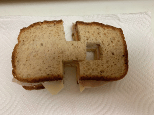 Game, Wife, and Her: My daughter hates it when her sandwich is not cut perfect in half. My wife had to up her game to annoy her.