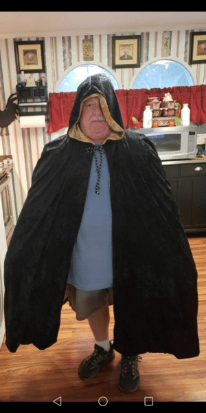 Dad, Halloween, and Mom: My mom made a warlock cloak for my son for Halloween. She made my dad wear it so she could send me a picture of it.