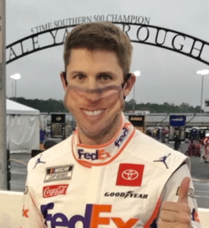 NASCAR driver Denny Hamlin wears a mask with his own face on it, before the race.: NASCAR driver Denny Hamlin wears a mask with his own face on it, before the race.