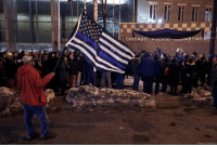 A man holds a police memorial American flag as he attends a candlelight vigil for Chicago Police Cmdr. Paul Bauer outside the Near North District headquarters.: NE  CHICAG  RTME A man holds a police memorial American flag as he attends a candlelight vigil for Chicago Police Cmdr. Paul Bauer outside the Near North District headquarters.
