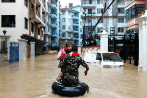 Nepali army carrying a child walks along the flooded colony in Kathmandu, on Friday, July 12, 2019.: Nepali army carrying a child walks along the flooded colony in Kathmandu, on Friday, July 12, 2019.