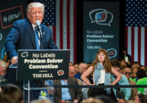 Apparently, Donald Trump, and Meme: No Labeils  Problem Selver  Cenventien  No Labels  Problem Solver  Convention  THEHILL, S brainstatic: owlmylove:  verticalbutthole:  Lauren Batchelder of Chester N.H. waits for Donald Trump to stop talking after interrupting her and to continue with her question on women's rights at the No Labels Problem Solver Convention in Manchester N.H. on Monday, October 12, 2015. (Glenn Russell, Burlington Free Press)  put this in the MOMA  I honestly thought this was a meme I never heard of, like someone photoshopped this indignant lady meme onto a picture, but apparently not.