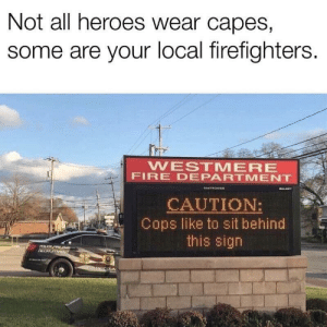 Fire, Heroes, and Cops: Not all heroes wear capes,  some are your local firefighters.  WESTMERE  FIRE DEPARTMENT  GALARY  DAKTRONICe  CAUTION:  Cops like to sit behind  this sign  POLCE FIRE EM  RECRUITMENT  nANYCOUN Not the heroes we wanted, but the heroes we deserved.