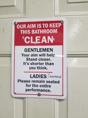 Help, Aim, and Closer: OUR AIM IS TO KEEP  THIS BATHROOM  CLEAN  GENTLEMEN  Your aim will help  Stand closer.  It's shorter than  you think.  LADIES NATHAN  Please remain seated  for the entire  performance My workplace has a sense of humor. Poor Nathan.
