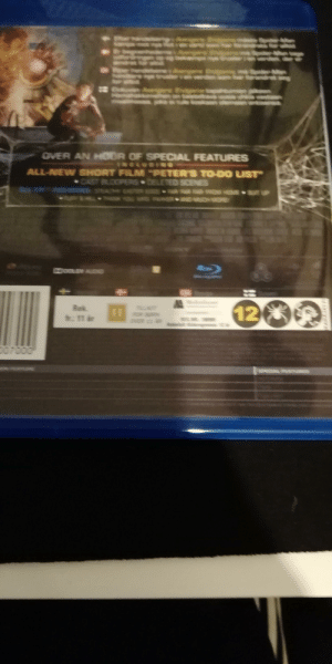 """Spider-Man Far from home blu rays info written on dark blue onto black color: OVER AN HOOR OF SPECIAL FEATURES  ALL-NEW SHORT FILM """"PETER'S TO-DO LIST  CAST BLOOPRS DELETED SCENES  12  Rek  ROR BRN  :11 ar  D07000  WARKIATE Spider-Man Far from home blu rays info written on dark blue onto black color"""
