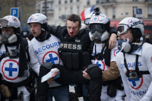 Symbolic. Medics helping journalist Julien Moreau after he was hit in the face by a tear gas grenade at this weekend's Yellow Vest protest in Paris.: P  Ai  Baby  SWISS+  ARMS  SECOURSPRESS  SE OURS  roYEN Symbolic. Medics helping journalist Julien Moreau after he was hit in the face by a tear gas grenade at this weekend's Yellow Vest protest in Paris.