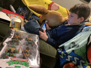 Surrounded by his Pokemon haul, TMNT unopened. Maybe I should tell them that they are Teenage Mutant Ninja Squirtles.: PokEMOy  nioxelodeon  TEENAGE MUTANT NINJA  परपरवपइड  1988  Fraxure  Guard Press  Guillotine Surrounded by his Pokemon haul, TMNT unopened. Maybe I should tell them that they are Teenage Mutant Ninja Squirtles.