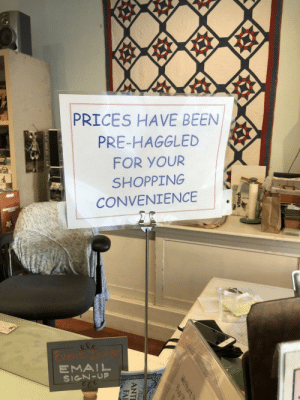 This sign in an antique store.: PRICES HAVE BEEN  PRE-HAGGLED  FOR YOUR  SHOPPING  CONVENIENCE  &le  vent Tnvit  EMAIL  SIGN-UP  vtech  WeHunt t  Buy it  Pela  ANTI  FAI This sign in an antique store.