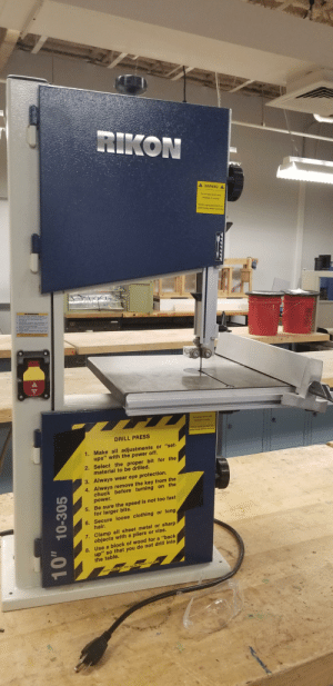 """Definitely a drill press: RIKON  A WARNING  Do not open doors while  bandsw is rumning  Always unplug bandsaw from  power supply before servicing  AWARNING  Aways wsAY tery s  De Ast eve jam d in  op  3. Matn prpr a  f  anthrt ngs  1 Ha wrk pere her ag  Do ret open dos while  bendswis uning  Always lg bandssw from  power supply belore servicing  DRILL PRESS  1. Make all adjustments or """"set-  ups"""" with the power off.  2. Select the proper bit for the  material to be drilled.  3. Always wear eye protection.  4. Always remove the key from the  chuck before turning on the  power.  5. Be sure the speed is not too fast  for larger bits.  6. Secure loose clothing or long  hair.  7. Clamp all sheet metal or sharp  objects with a pliers or vise.  8. Use a block of wood for a """"back  up"""" so that you do not drill into  the table.  SAFETY RUZES INC 3727 Joun Dr.Wabecloo, lowa 50702  10-305 Definitely a drill press"""