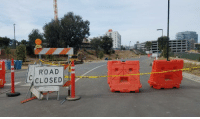 These barriers look like they are in the final steps of a very close foot race.: ROAD  CLOSED These barriers look like they are in the final steps of a very close foot race.