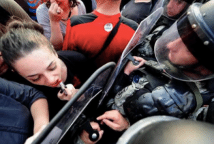 Riot, Target, and Tumblr: rosacarinaviola:  sixpenceee:  A woman protestor in Macedonia uses a riot shield as a mirror to reapply her lipstick.  Iconic