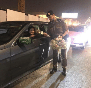 Police, Drive, and Saudi Arabia: Saudi police officers hand out roses to female drivers. (Today is the first-day women can legally drive in Saudi Arabia)