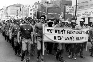 """Vietnam veterans protesting the Vietnam war, """"We won't fight another rich man's war"""" 1970: SAVE  ONE  WAY  CНЕCKS  CASHED  24 HOUR  AUTO TAGS MONEY ORDERS  M.H.CARSON& SON  RE  MSURANCE MORTON N. NEUFELD  REAL ESTATE  STREET  MC  APPRAISALS  533  533  CAR V  HEAL ESTATE  WE WONT FIGHT ANOTHE  RICH MAN'S WAR!! Vietnam veterans protesting the Vietnam war, """"We won't fight another rich man's war"""" 1970"""