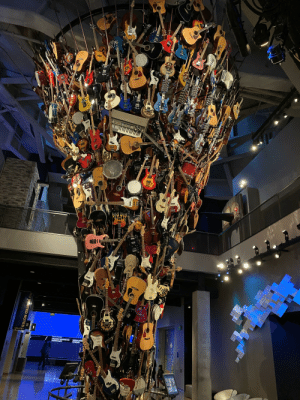 Sculpture of Guitars - I think it's 500+ guitars mounted as a sculpture. Several are connected to computer controlled devices that play them into headsets below. Image shot at the Museum of Pop Culture in Seattle.: Sculpture of Guitars - I think it's 500+ guitars mounted as a sculpture. Several are connected to computer controlled devices that play them into headsets below. Image shot at the Museum of Pop Culture in Seattle.