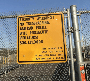 Am I a train?!: SECURITY WARNING!  NO TRESSPASSING,  AMTRAK POLICE  WILL PROSECUTE  VIOLATORS!  800.331.0008  lf  THE TRACKS ARE  ONLY FOR TRAINS.  IF YOU CAN READ THIS  YOU ARE NOT A TRAIN.  WARN Am I a train?!