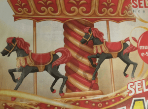 Christmas, Horses, and Black: SEL  о Неа  mu  e-s  SEL The carousel horses of this christmas themed ad look like they have heads of demonic hogs... The black & red colour combo is not helping.