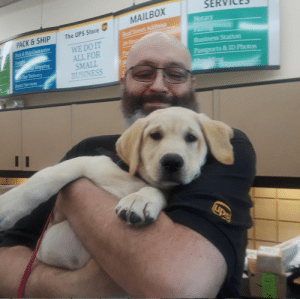 ups-dogs:This is Chris who works at my UPS store, he's always happy to hug my Service pup in training.: SERVICES  The UPS Store  WE DO IT  ALL FOR  SMALL  BUSINESS  PACK & SHIP  ack& Ship Guarantee  Day Delivery  ID Photos  Postal Services ups-dogs:This is Chris who works at my UPS store, he's always happy to hug my Service pup in training.