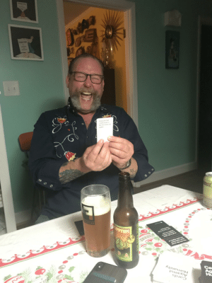 I took a pic of my hubs playing Cards against humanity. He's a joy.: SHOWEAS  Pulling the boft  cheeks apart so  the fart comes out  quieter  the quiet dignity of  vever understand  You city follk would  Malibu, I'm into  is Kendra,Ilive in  Ca  Ag  Hu  *ou pooe  Humanity  Against  Cards  HOlder  ULLSTEAM  INDIA  PALE ALE I took a pic of my hubs playing Cards against humanity. He's a joy.
