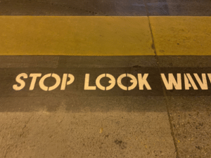 Cross walk wording in Santa Monica seems to suggest I should look right, away from oncoming traffic.: STOP LOCOK WAV Cross walk wording in Santa Monica seems to suggest I should look right, away from oncoming traffic.