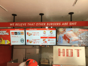 This burger restaurant in South Korea.: T.  WE BELIEVE THAT OTHER BURGERS ARE SHIT  Beverages  Billonbax Combe  Sliders  WERRY  RSTMAS  Billionbox Pack  Single combo  Aillio  Sprite  Rill  L22.C  8.5  Saft drink 1.8  Sngle 2.9  Double bole 3.9  빌리언팩  ETHOIA  Sides  Double-Double  combo  Bainchan  Heineken 3.0  beer  loka un 2.1  9.9  Fr  A  18  1.0  llion Tenders 3.4  15%2  HIT  Rillionh  Allorbor This burger restaurant in South Korea.