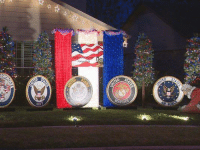 The Schriever family wanted to do something special with their Christmas decorations. Rather than Santa riding on a sleigh, their display features Santa kneeling before six medallions, five representing a branch of the military and one for first responders.: terest-ii The Schriever family wanted to do something special with their Christmas decorations. Rather than Santa riding on a sleigh, their display features Santa kneeling before six medallions, five representing a branch of the military and one for first responders.