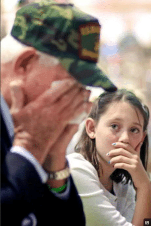 The photo is of a young granddaughter watching her grandfather break in to tears at her schools Veterans Day assembly.: The photo is of a young granddaughter watching her grandfather break in to tears at her schools Veterans Day assembly.