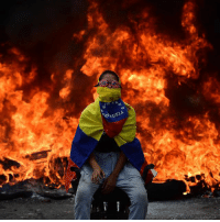 """Life, Memes, and Protest: UELA 25 APR: A Venezuelan opposition activist isits in front of a burning barricade during a demonstration against President Nicolas Maduro in Caracas. The latest violence raised the death toll to 24 in three weeks of protests. Public defender Tarek Saab said several others were seriously injured and """"between life and death"""". The latest protests were sparked by the decision of the Supreme Court to take over the powers of the opposition-dominated National Assembly. The court's reversal of the ruling was not enough to stop a wave of demonstrations, with opposition supporters calling for immediate elections. On Monday a man was shot dead in a pro-government demonstration in the city of Merida. Two other men - one in Merida and another in the nearby town of Barinas - also died, though it is not clear what side of the protests they were on. Merida state governor Henrique Capriles, one of Venezuela's main opposition leaders, tweeted that """"paramilitary groups"""" were responsible for the killings. PHOTO: RONALDO SCHEMIDT-AFP BBCSnapshot =photojournalism protest demonstration Caracas Venezuela"""