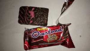 Facepalm, Black, and Cake: uerload  BLACK  QUAKE  FEREST  a Filling  Choco-Coated Choco Cake with Cherry-Flavored Jam and  TS BASE M  CER  INGRE  JACKNJILL Never Trust The Packaging
