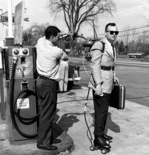 scifiseries:  A salesman has his motorized roller skates refueled at a gas station in 1961.: UN  USE AS A  CONTAINS  LEAD scifiseries:  A salesman has his motorized roller skates refueled at a gas station in 1961.