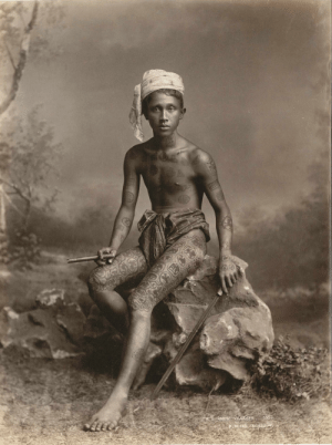Tattoos, Sword, and Burma: URMESE VILLAGER  50  P. KLIER A young man with traditional tattoos holding a sword and a cheroot (cigar), Burma, 1895