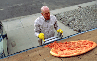US GI grimaces as he finds the corpse of Italian soldier laid out on roof. Sicily 1943.: US GI grimaces as he finds the corpse of Italian soldier laid out on roof. Sicily 1943.