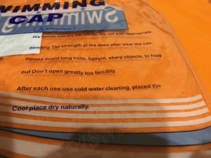 Instructions for a swimming cap: VIMMIN  PARMIW  CG  AInstructions  His hands into his hat inside, the net with appropriate  bending The strength of the open after wear the can.  r  Please avoid long nails, hairpin, sharp objects, to hold  out Don't open greatly too forcibly.  After each use use cold water cleaning, placed Yin  Cool place dry naturally. Instructions for a swimming cap