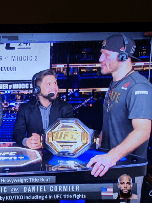 Dad, Ufc, and Looking: VS MIOCIC 2  EVOUR  IER MIOCIC 2  ATE  KIFC  Heavyweight Title Bout  IC DEF. DANIEL CORMIER  by KO/TKO including 4 in UFC title fights  7 Triple C looking up at Stipe like he's his dad