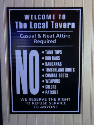 I can't tell if this sign is insinuating something...: WELCOME TO  The Local Tavern  Casual & Neat Attire  Required  TANK TOPS  DOO RAGS  BANDANAS  TIMBERLAND BOOTS  COMBAT BOOTS  WEAPONS  COLORS  PATCHES  NO  WE RESERVE THE RIGHT  TO REFUSE SERVICE  TO ANYONE I can't tell if this sign is insinuating something...