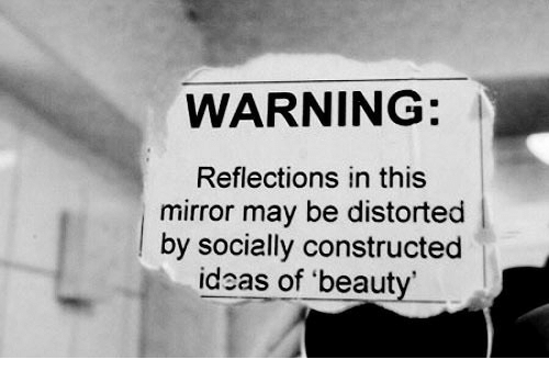 Mirror, Ideas, and May: WARNING:  Reflections in this  mirror may be distorted  lby socially constructed  ideas of 'beaut